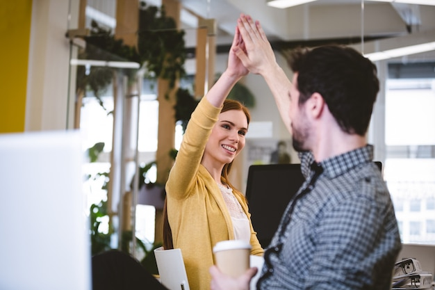 Businesswoman giving high-five to male coworker
