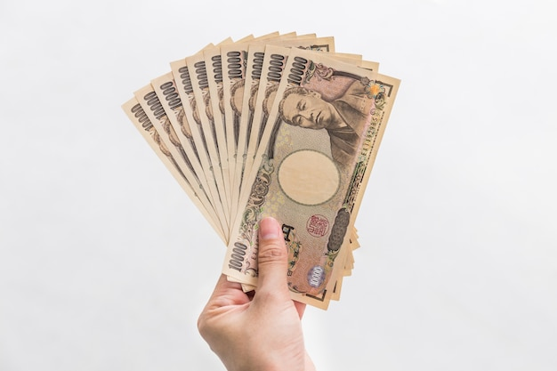 Businesswoman giving money and holding 10,000 japanese yen money in hand isolated on white