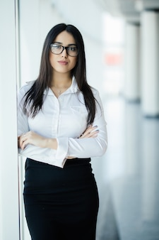 Businesswoman in glasses crossed hands portrait in office with panoramic windows. business concept