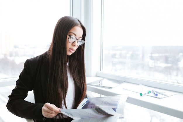 Businesswoman in glasses reading magazine near the window at office