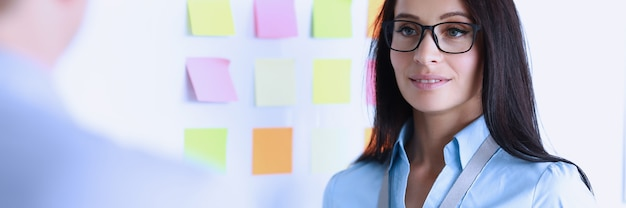 Businesswoman in glasses stands next to white board opposite colleague. communication of partners on business forums concept