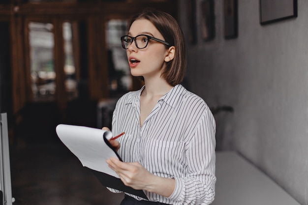 Businesswoman in glasses and white classic shirt takes notes in papers and poses in office.