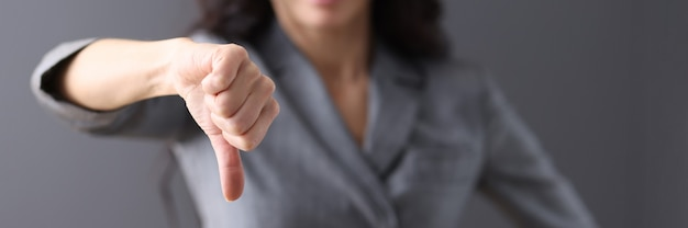Businesswoman in gray suit holds her thumb down unsuccessful business decisions concept