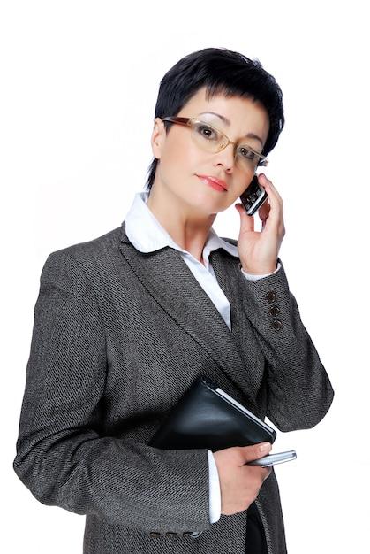 Businesswoman in grey business suit calling by mobile phone