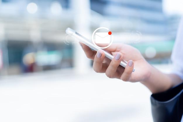 開いている未読メールの実業家の手保持スマートフォンデバイス