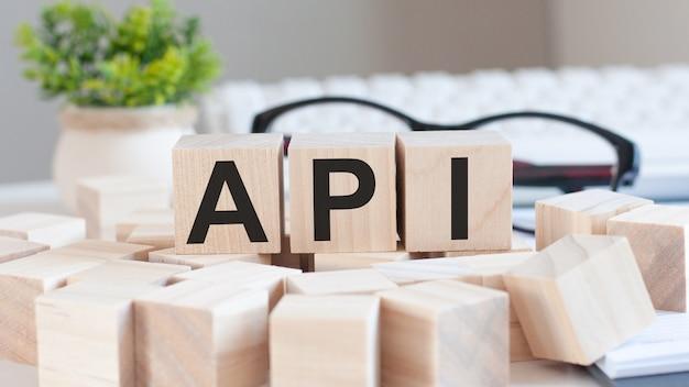 木製の立方体ブロックでapiワードを持っている実業家の手。コミュニケーションの概念。 api-アプリケーションプログラミングインターフェイス