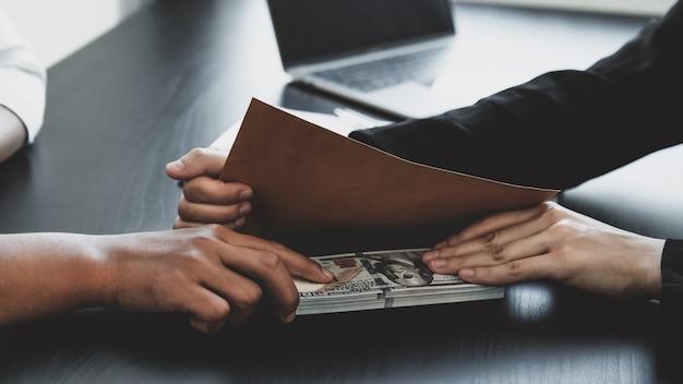 Деловая женщина держит взятку в руке, чтобы чиновники подписывают контракты на бизнес-проекты, кладут деньги в конверт, идеи коррупции и противодействия взяточничеству.