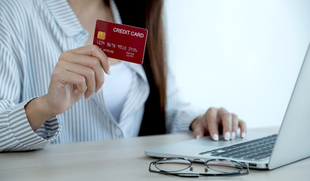 Businesswoman hand holding credit card to online shopping from home, payment e-commerce, internet banking, spending money for next holidays.