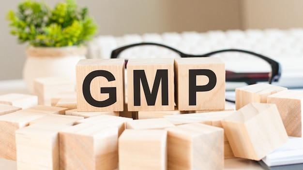 Рука коммерсантки держа слово gmp с деревянным блоком куба. слияния и поглощения, информация