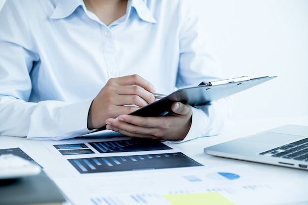 Businesswoman hand holding a pen and analysis the chart with laptop at the home office for setting challenging business goals and planning to achieve the new target.