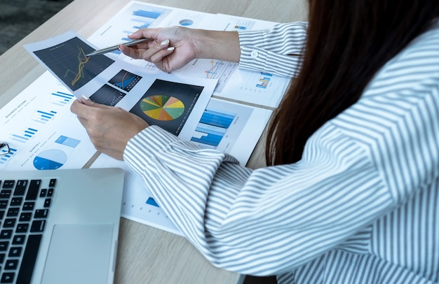Businesswoman hand holding pen and analysis the chart with laptop at the office for setting challenging business goals and planning to achieve the new target.