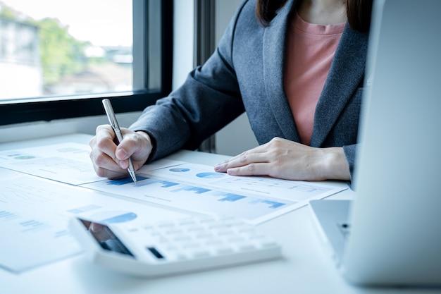 Деловая женщина рука анализ пера граф с калькулятором и ноутбуком в домашнем офисе