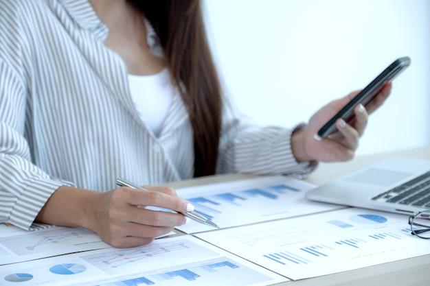 Деловая женщина рука ручку и анализ диаграммы с ноутбуком в офисе для постановки сложных бизнес-целей и планирования для достижения новой цели.