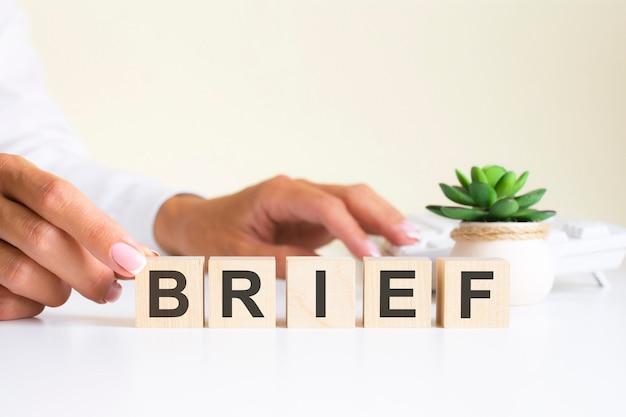 Рука коммерсантки держа деревянный блок куба с кратком словом дела на предпосылке таблицы. концепция миссии, видения и основных ценностей
