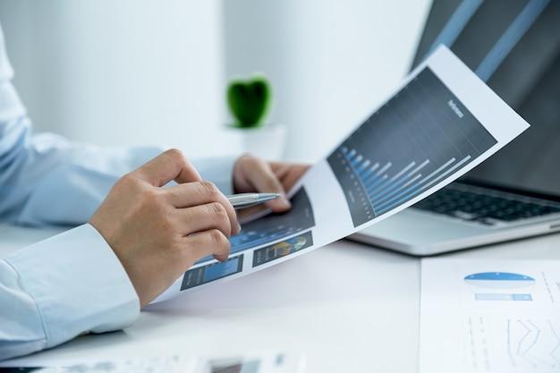 Деловая женщина указывает на график и анализирует с помощью ноутбука в домашнем офисе для постановки сложных бизнес-целей и планирования для достижения новой цели.