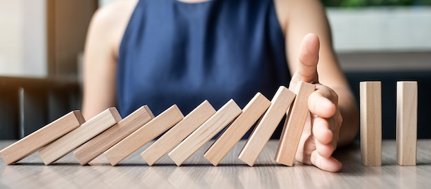 Businesswoman hand stopping falling wooden dominoes
