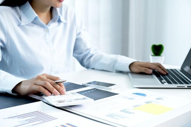 사업가 손 사용 계산기 및 분석 도전적인 비즈니스 목표를 설정하고 새로운 목표를 달성하기 위해 계획을 홈 오피스에서 노트북으로 차트.