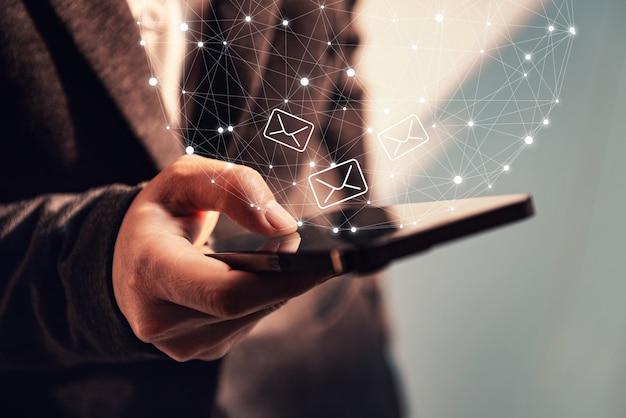 メールアイコンとスマートフォンを使用して実業家の手