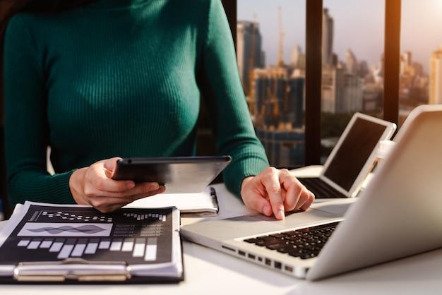 コンセプトとしてスマートフォンやタブレットを使用して新しい現代のコンピューターで作業する実業家の手