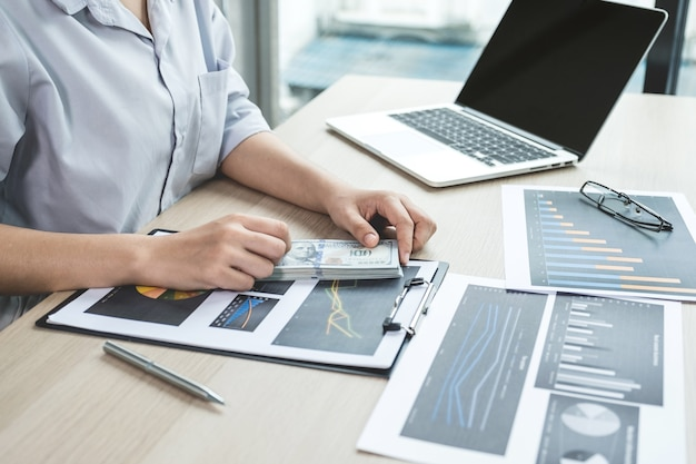 Businesswoman hands count dollar note and analysis the chart with laptop at the office for setting challenging business goals and planning to achieve the new target.