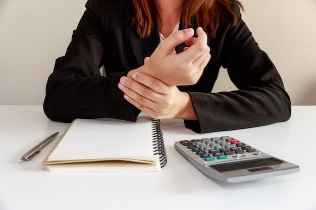 Businesswoman hands pain on desk office syndrome with notebook and calculator.