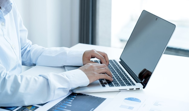 Businesswoman hands typing keyboard and analysis the chart with laptop at the home office for setting challenging business goals and planning to achieve the new target.