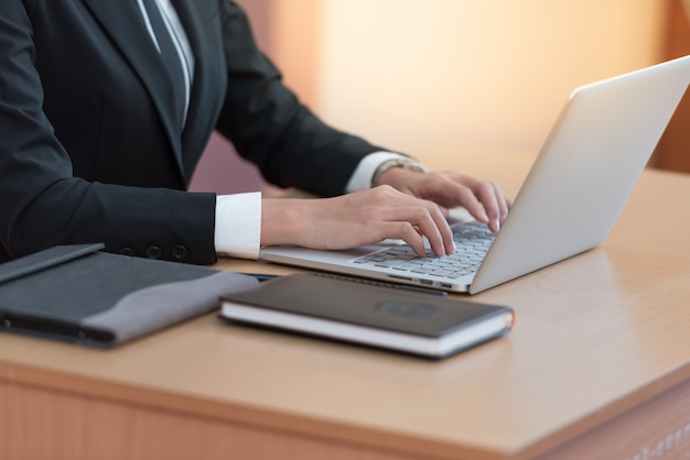 Businesswoman hands typing on laptop keyboard at desk.