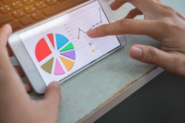 Businesswoman hands using data graph report in smartphone for checking analyze marketing f