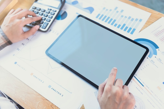 空白の画面でタブレットを使用して実業家の手。コンピュータータブレットモニターのモックアップ。デザインやテキストの準備ができたコピースペース。