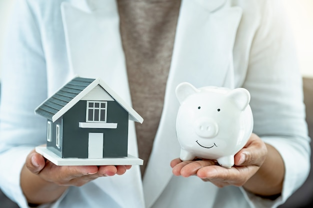 Businesswoman hands in white suit holding home model and piggy bank.