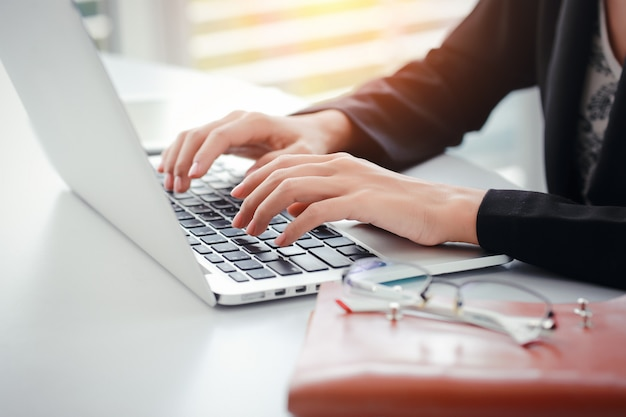 Businesswoman hands with glasses using computer