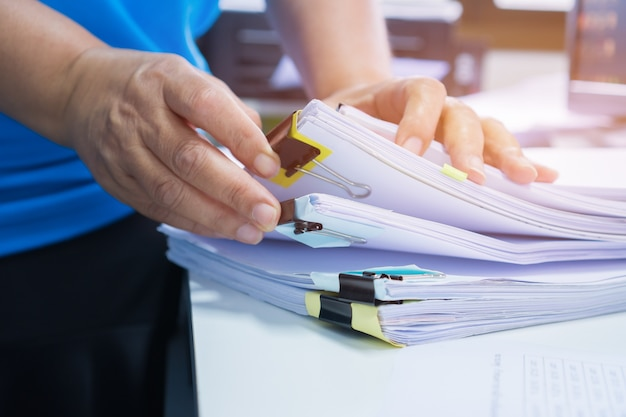 Businesswoman hands working in stacks paper files for searching and checking documents