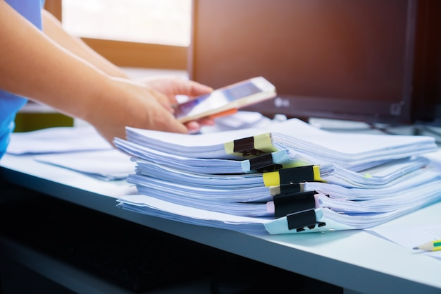 Businesswoman hands working in stacks paper files