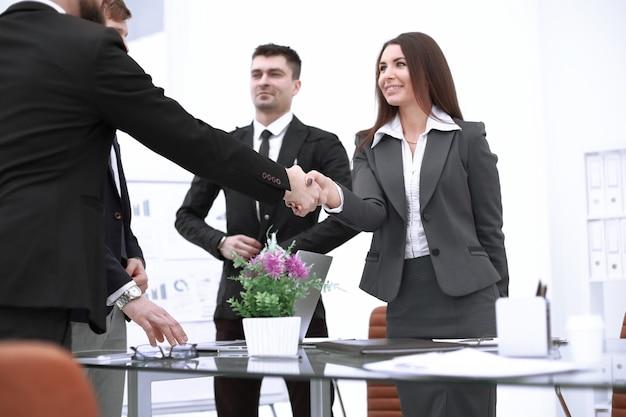 Businesswoman handshake with business partner in modern office.