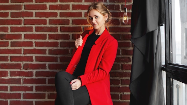 Businesswoman happy smile wear red jacket - business woman over office brick wall