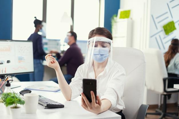 얼굴 마스크를 쓰고 스마트폰을 사용하여 기업 화상 회의를 하는 사업가. 코로나바이러스로 인한 세계적 대유행 동안 사회적 거리를 존중하면서 일하는 동료들.