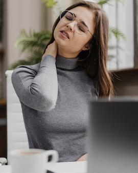 Деловая женщина, имеющая боль в шее при работе из дома