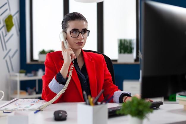 Деловая женщина разговаривает по телефону с финансовым консультантом