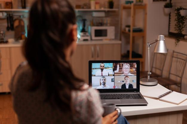 사업가는 자정에 집 부엌에서 노트북을 사용하여 팀과 화상 회의를 합니다. 현대 기술을 사용하는 기업 회의, 늦은 밤 노트북, 기술, 기관, 고문, 작업, 토론