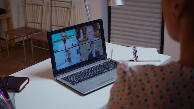 자정에 집 부엌에서 노트북을 사용하여 팀과 화상 회의를 하는 사업가입니다. 현대 기술 네트워크 무선을 사용하여 자정에 가상 회의에서 초과 근무를 하는 여성