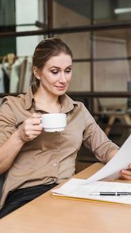 사업가 커피를 마시고 서류를 읽고