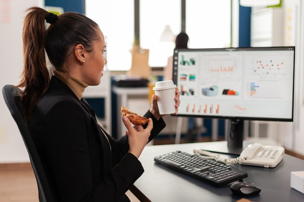 Businesswoman having delivery food order on desk during takeout lunchtime working in business company office