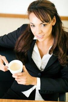 Businesswoman having a double espresso