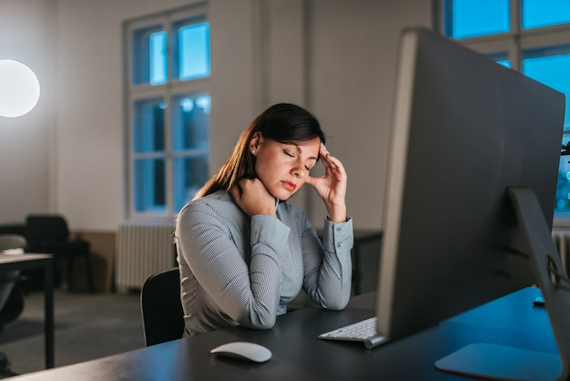 Businesswoman having migraine while working overtime.
