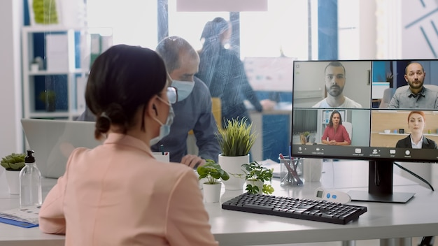 코로나바이러스 전염병 동안 의료용 안면 마스크를 쓰고 온라인 화상 통화 회의를 하는 사업가. 사회적 거리를 존중하는 원격 팀과 함께 새로운 일반 사무실에서 일하는 프리랜서