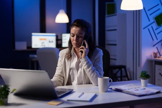 Деловая женщина, имеющая телефонный звонок в стартовом офисе поздно ночью, работает над маркетинговым проектом, чтобы соблюсти срок