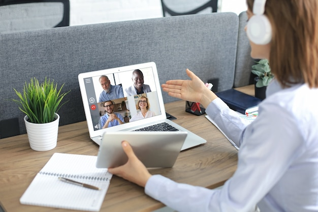 Businesswoman in headphones talking to her colleagues in video conference. multiethnic business team working from office using laptop, discussing financial report of their company on tablet..