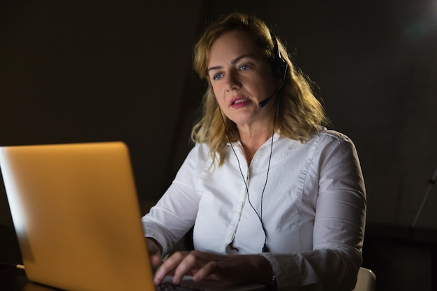 Businesswoman in headset using laptop computer