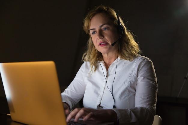 Donna di affari in cuffia avricolare facendo uso del computer portatile