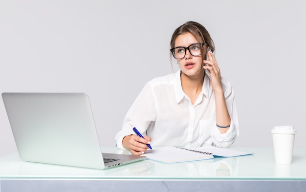 Businesswoman at her working desk with laptop and talking phone isolated on white background